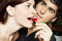 Close_up of a young man feeding a cherry to a young woman