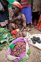 A woman sitting on the ground, selling beans, with people around her, while only their feet and legs are seen, Ethiopia, East Africa.