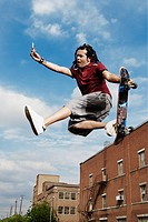 Teenage boy doing skateboard jump
