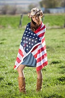 Beautiful cowgirl wrapped in American flag