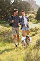 Couple walking their dogs in the countryside