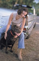 woman with chocolate labrador retriever in front of antique car