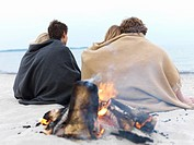 Romantic couples sitting by bonfire at beach