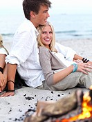 Portrait of happy young couple sitting by bonfire at beach in summer