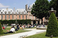 Parisians enjoy the sun in Square Louis XIII in Place des Vosges in Paris