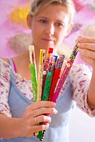 Woman holding a selection of different chopsticks