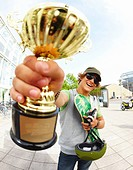 Happy handsome young man holding first prize gold cup