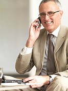 Portrait of a successful senior business man using cell phone