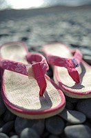 A pair of pink flip flops shoes on a pebble beach, summer UK