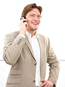 Cheerful businessman using mobile phone against white background