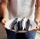 Man holding plate of fresh mackerel