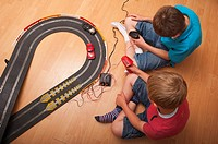 A  picture of two boys  6 & 10  playing with a Hornby Scalextric racing car set game in the Uk