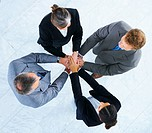 Handshake and teamwork Four business people making a pile of hands in a light and modern office environment