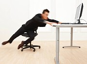 Business man rushing towards computer on desk