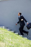 Businessman running up a stairway (thumbnail)