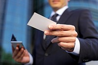 Man holding a calling card into the camera