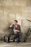 Businessman drinking coffee in crouched position (thumbnail)