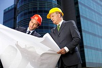 Two Businessman with hardhats watching a plan