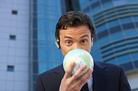 Businessman covering his face with an earth ball