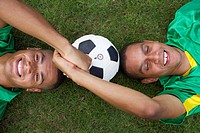 Two Brazilian kickers lying on grass, holding hands