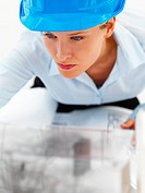 Closeup of a young female architect working on blue prints
