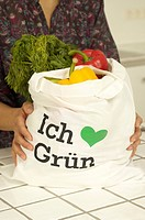 Woman with shopping bag filled with organic products