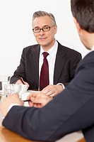 Two businessmen talking in conference room, Munich, Bavaria, Germany
