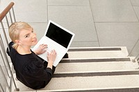 Woman using laptop on stairs, Munich, Bavaria, Germany