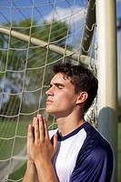Kicker praying beside a goal