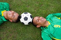 Two Brazilian soccer players lying on grass