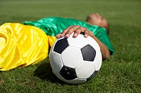 Exhausted Brazilian soccer player lying on grass, hand resting on ball