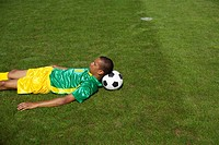Exhausted Brazilian soccer playing lying on grass