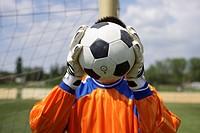 Goalkeeper covering face with soccer ball