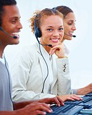 Closeup of happy young office workers sitting with headsets
