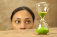 Woman looking at hourglass with green sand (thumbnail)