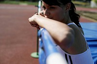 Woman leaning on a high jump bar