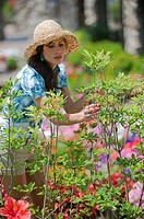 Brunette woman in casural summer clothes looking at plants at a flower market.