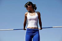 Woman standing in front of a high jump bar