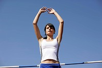 Woman in front of a high jump bar