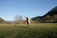 Mature man running over a meadow with a kite (thumbnail)