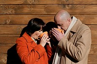 Mature couple standing in front of a wood wall and drinking coffee