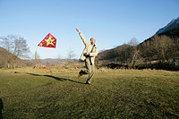 Mature man running over a meadow with a kite