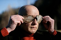 Man hiding his eyes with leaves