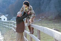 Mature man helping woman to climbing over a fence