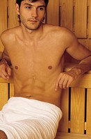 Darkhaired Man resting his Arms on a wooden Bench _ Heat _ Sauna _ Wellness