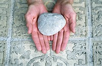 Woman holding a Stone over an ornate Ground _ Meditation _ Element