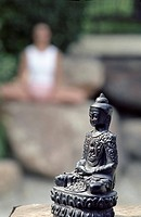 Buddha_Statue in front of a Woman who is doing Yoga on a Rock _ Buddhism _ Meditation