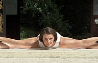 Darkhaired Woman with straddled Legs bending forward _ Yoga _ Flexibility _ Physicalness