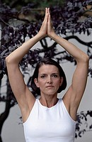 Darkhaired Woman lifting her Arms up _ Yoga _ Tree