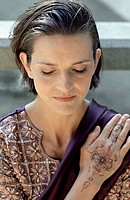 Darkhaired Woman in a Saree putting one with Henna painted Hand on her Shoulder _ Meditation _ Tradition